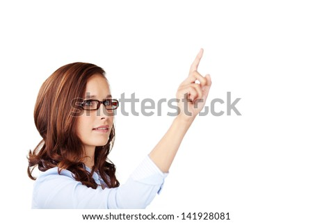 Attractive young woman wearing glasses pointing to blank white copyspace or touching a virtual interface with her finger - stock photo