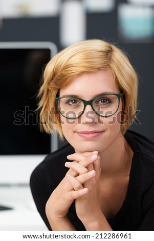 Attractive young woman wearing glasses resting her chin on her hand looking into the camera with a thoughtful smile - stock photo