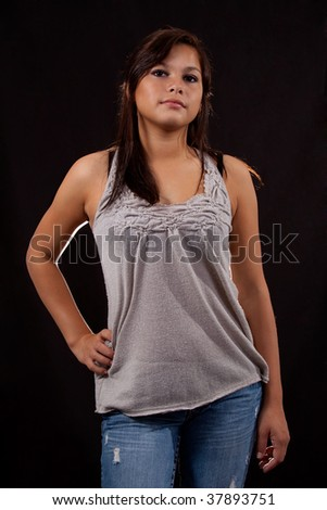 Attractive young woman wearing jeans and grey top standing over black
