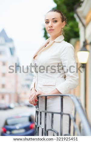 Attractive young woman wearing white jacket posing outdoors - stock photo