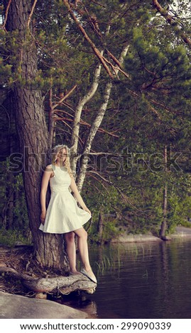 Attractive young woman wearing white summer dress and she leans towards the pine, sunny summer day, lake on background, cross processed image - stock photo