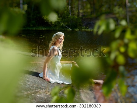 Attractive young woman wearing white summer dress, sunny summer day - stock photo