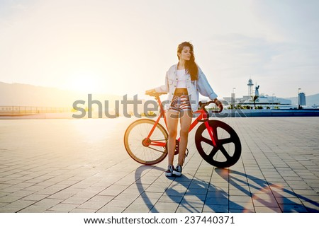 Attractive young woman win fixed gear bike posing outdoors with soft sunset light on background, pretty young brown haired woman standing with her modern pink bicycle at sunset, stylish hipster woman - stock photo