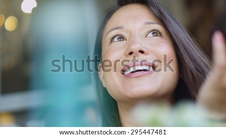Attractive young woman with a cheerful face as she talks to an unseen friend - stock photo