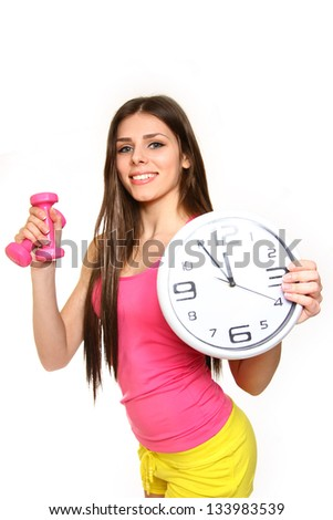 Attractive young woman with a clock and dumbbells on white background - stock photo
