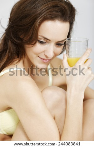 Attractive young woman with a glass of fresh Orange juice in her underwear - stock photo