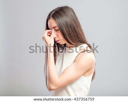 Attractive young woman with a headache pinches the bridge of her nose with a pained expression isolated on gray - stock photo