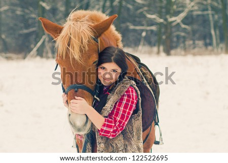 Attractive Young Woman with a Horse the Snow - stock photo