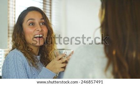 Attractive young woman with a look of laughter on her face as she listens to her friend - stock photo