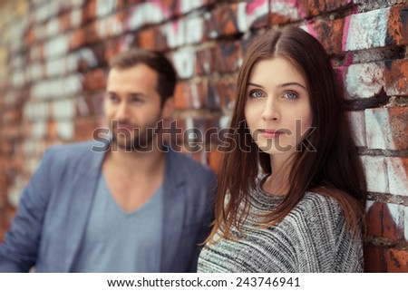 Attractive young woman with a serious expression standing against a graffiti covered brick wall in an urban street alongside her husband or boyfriend looking at the camera - stock photo