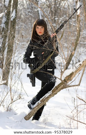 Attractive young woman with a sniper rifle in winter forest