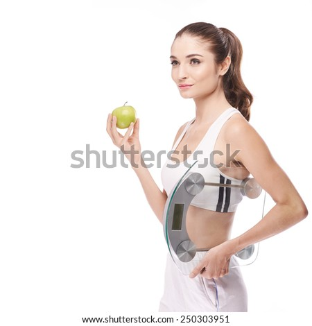 Attractive young woman with apple and scales in her hands: dieting concept - stock photo