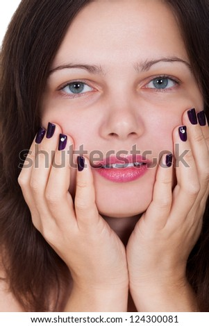 Attractive young woman with beautiful purple nails holding her hands to her cheek - stock photo