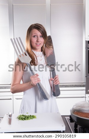 attractive young woman with big fork and knife - stock photo
