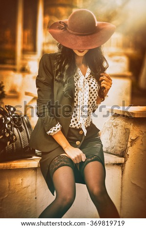 Attractive young woman with burgundy colored large hat in autumnal fashion shot. Beautiful lady in black outfit with short skirt and sexy stockings sitting on marble wall. Elegant brunette outdoors. - stock photo