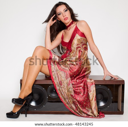 attractive young woman with colorful long dress sitting on a loudspeaker, white background - stock photo