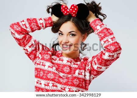 Attractive young woman, with curly dark hair, wearing in red Christmas sweater and mouse ears in her head, smiling with hands on her hair, on the white background, in studio, waist up - stock photo