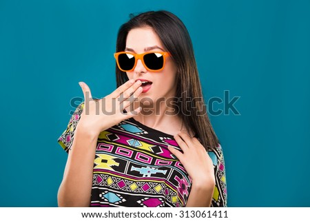 Attractive young woman, with dark hair, wearing in colorful shirt and orange sunglasses, posing on the blue background, in studio, waist up - stock photo