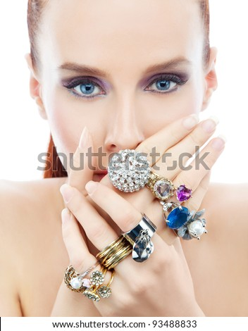 Attractive young woman with diamonds on the hands looking to the camera on the white background