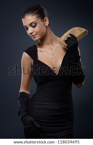 Attractive young woman with fancy rhinestones makeup posing in elegant evening dress with handbag. - stock photo