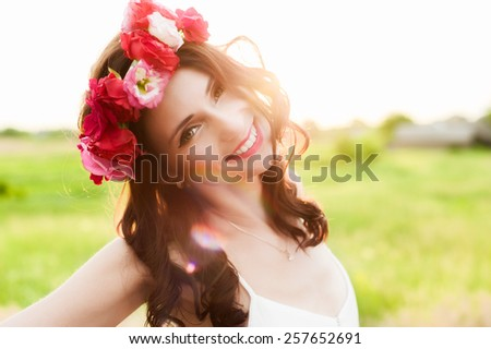 Attractive young woman with floral wreath on her head and sunset on background. Shallow DOF, with lense flare that made intentionally. - stock photo