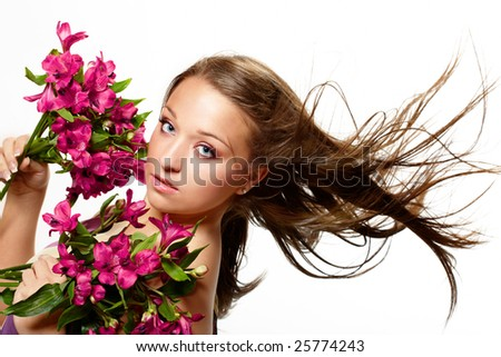 Attractive young woman with flowers, wind in hair, isolated on white