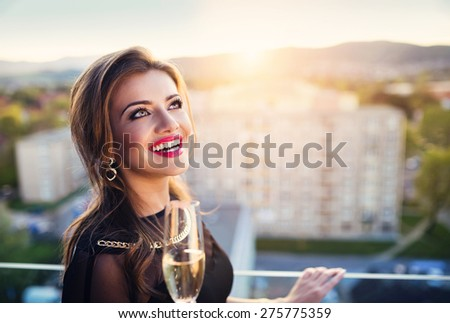 Attractive young woman with glass of champagne in a bar - stock photo