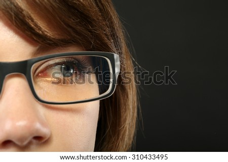 Attractive young woman with glasses on gray background - stock photo