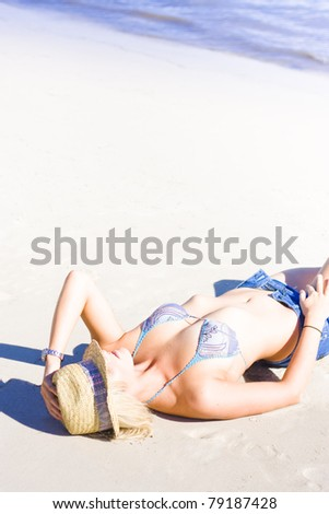 Attractive young woman with hat lying on back at beach - stock photo