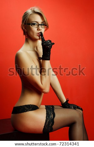 Attractive young woman with her finger up on a red background - stock photo