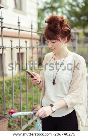 Attractive young woman with her hair in a bun standing holding her bicycle checking her mobile phone - stock photo