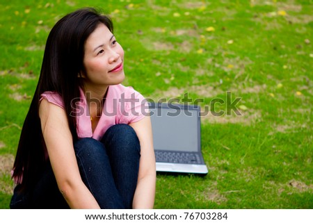 Attractive young woman with her notebook on green grass.