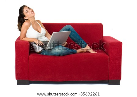 attractive young woman with laptop working on couch at home - stock photo