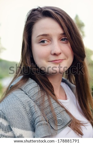 Attractive young woman with long brown hair and an amused smile looking sideways off frame, closeup portrait of her face - stock photo