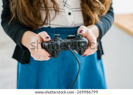 Attractive young woman with long curly brunette hair on a background window playing computer game at home. - stock photo