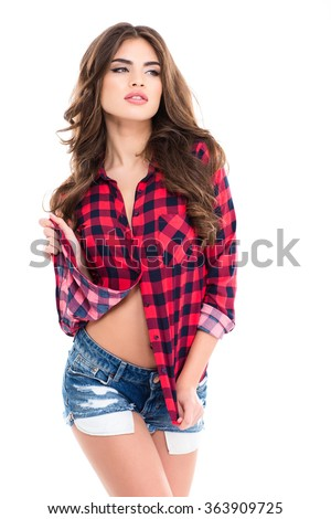 Attractive young woman with long curly hair in checkered shirt and jeans shorts posing over white background - stock photo
