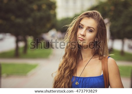 Attractive young woman with long curly hair poses in blue summer dress