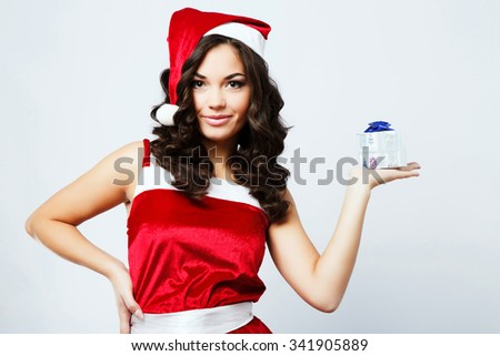 Attractive young woman, with long curly hair, wearing in red santa costume, holding present in her hand, on the white background, in studio, waist up - stock photo