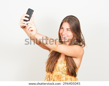 attractive young woman with long hair takes a selfie - stock photo