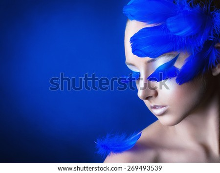 Attractive young woman with make-up with bright blue feathers on a blue background - stock photo