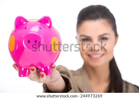 Attractive young woman with moneybox isolated on a white background. Focus on moneybox.