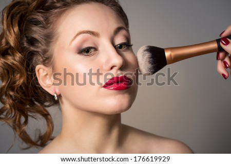Attractive young woman with red lips, professional make-up and make-up brush.