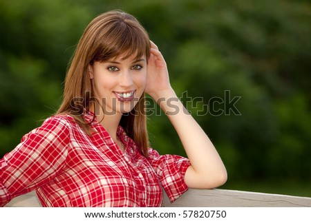 Attractive young woman with red top leaning on a fence - stock photo