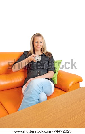 Attractive young woman with remote control on a sofa in her living room - stock photo