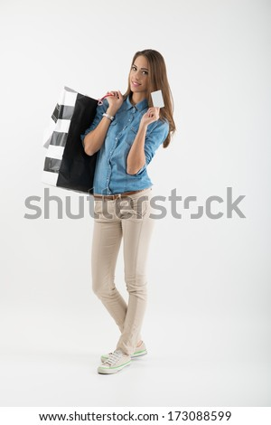 Attractive young woman with shopping bags and credit card - stock photo