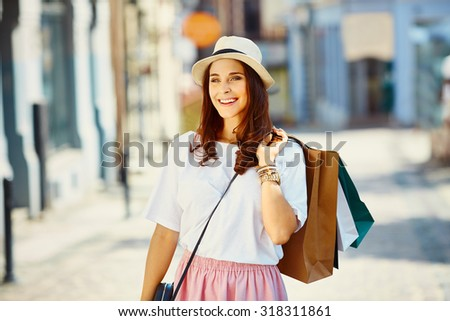 Attractive young woman with shopping bags on the street - stock photo