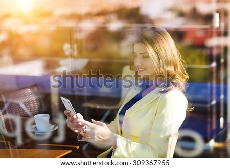 Attractive young woman with smart phone in a cafe - stock photo