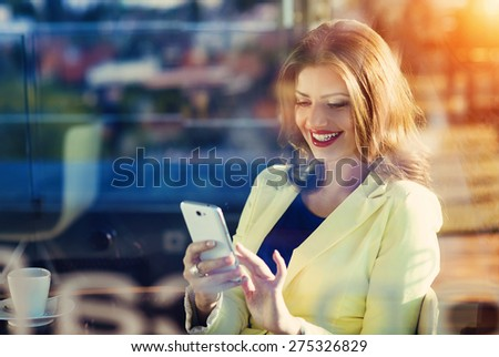 Attractive young woman with smart phone in cafe - stock photo