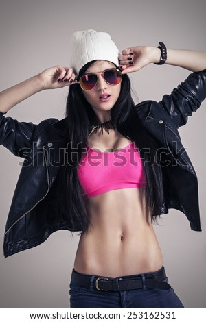 Attractive young woman with sunglasses. casual modern wear style. Fashion posing photoshoot. - stock photo