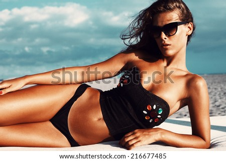 attractive young woman with sunglasses in bikini and black top lie and take sunbath on beach - stock photo